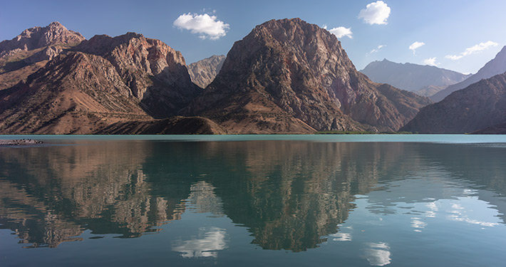 Dark sandy coloured mountains are reflected in the milky blue water of Iskanderkul, the biggest lake in Tajikistan's Fann Mountains