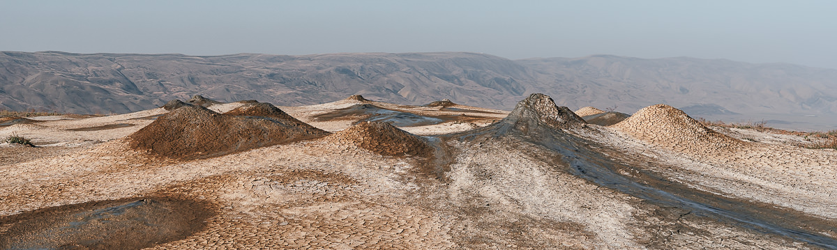 The ground is pockmarked by clusters of variously sized mud volcanoes, some more lively than others