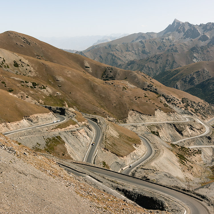A road slaloming down from Taldyk Pass with mountai