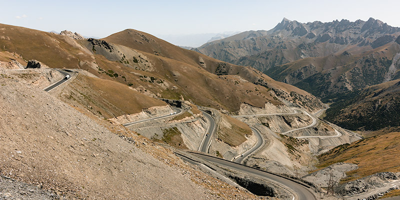 A road slaloming down from Taldyk Pass with mountains rising behind