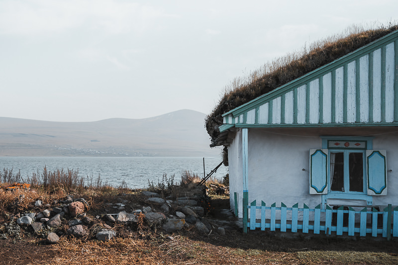 A whitewashed, turf roofed house is decorated colourfully with green and blue stripes, sitting on the shores of Paravani Lake on the Javakheti Plateau in Georgia