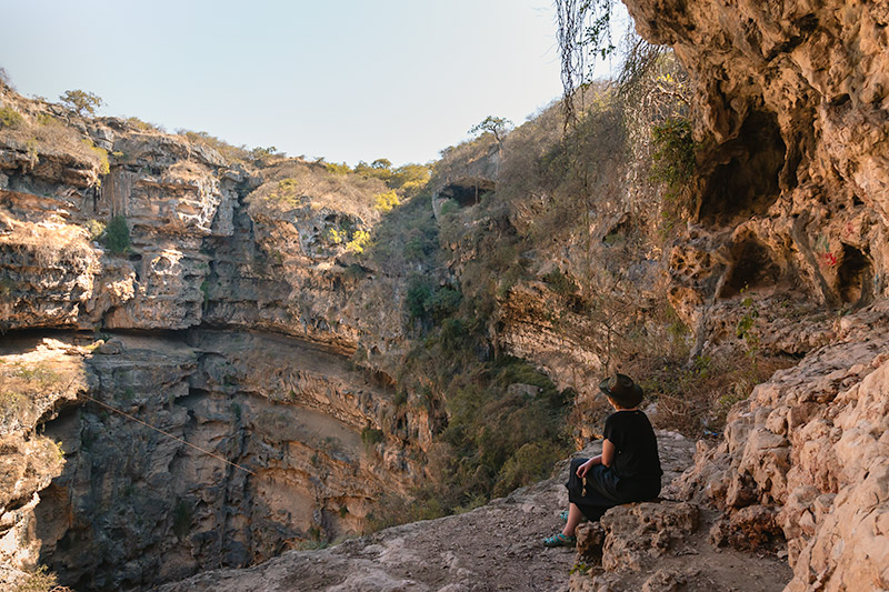 A person looks out at the yawning chasm of the Tawi Atair sinkhole from a ledge halfway down