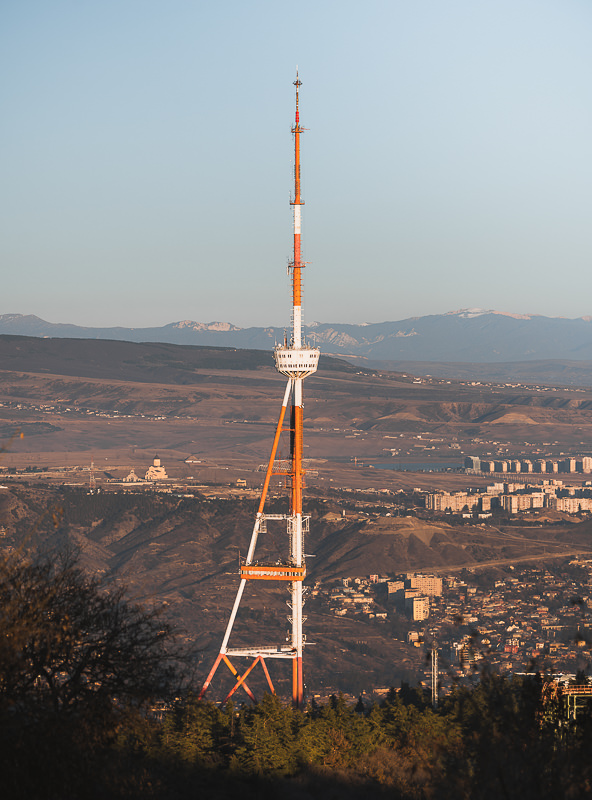 The Tbilisi TV Tower is glowing golden just before sunset, seen from the Tbilisi to Kojori hiking trail