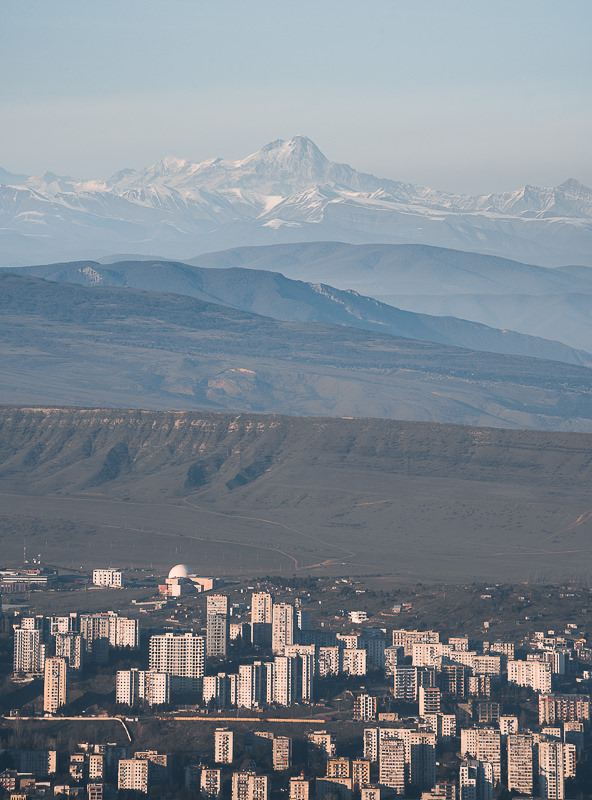 The late afternoon sun lights up Tbilisi apartment buildings with Mount Kazbek seen in the hazy distance