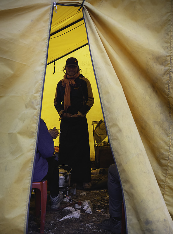 A young Tibetan man, serving hot drinks to trekkers, stands in the doorway of a big yellow tent on the way up to the Larke Pass