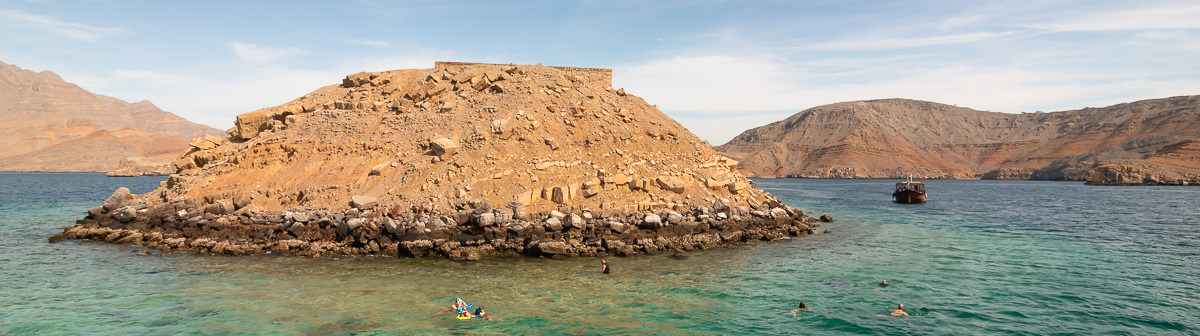 People snorkelling in the aquamarine water round Telegraph Island in the waters off the coast of Musandam