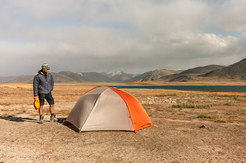 A person stands next to their gray and orange tent on the shores of Kokjigit Lake in Tajikistan