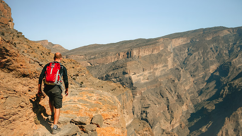 Aperson with a small red backpack sets out on the balcony walk at Oman's Grand Canyon, below Jebel Shams, Oman's highest mountain. The narrow rocky path falls off to the right in a sheer drop. This is one of the best places to visit in Oman.