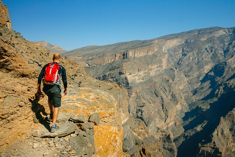 Striding out onto the path above Oman's Grand Canyon, Jebel Shams rising high on the other side