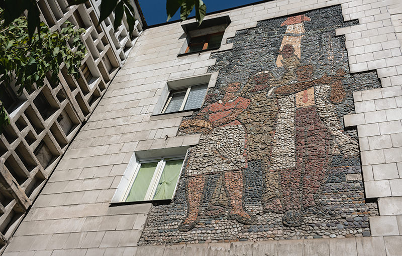 A Soviet era pebble mosaic called 'Labour' on the external wall of an apartment block in Bishkek