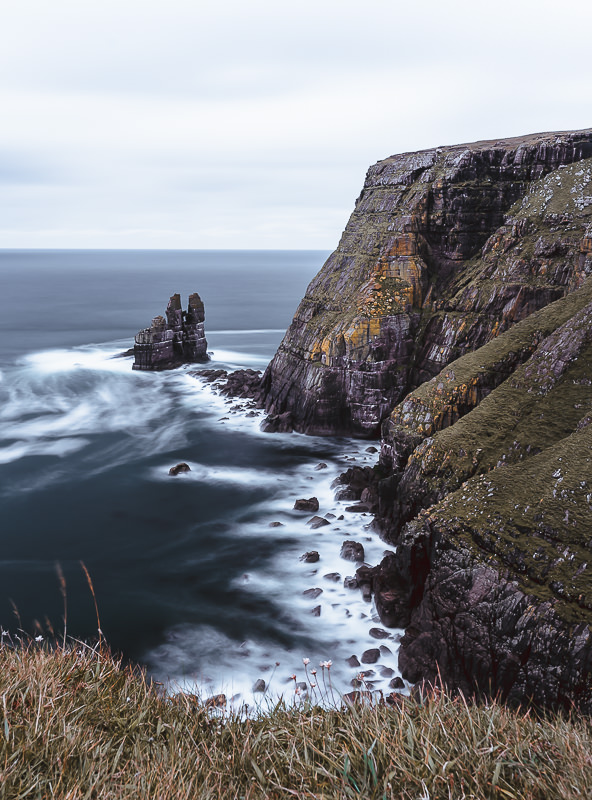 A distinctive sea stack called 'The Cathedral' sits below towering cliffs at Kearvaig Bay on the north coast of Scotland