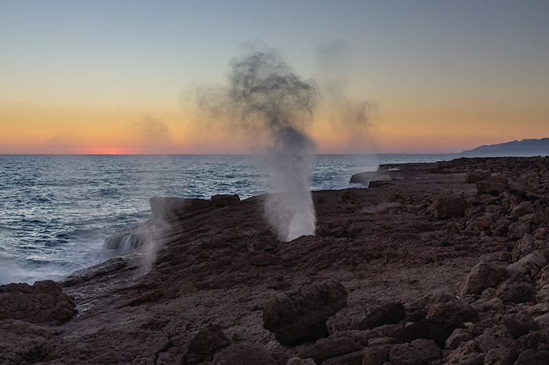 The blowholes at Fins in action, blasting up from the rocks while the sun pushes up over the horizon and the waves crash in. One of the many amazing sights to see at Campsites in Oman.