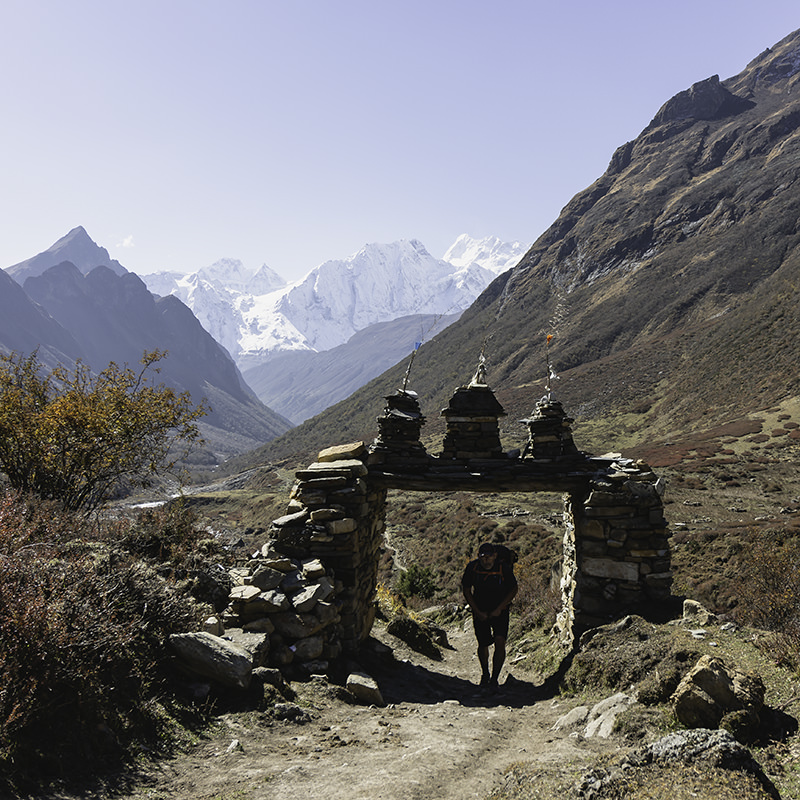 A hiker walks through a trail gate with snowy mountains in the background