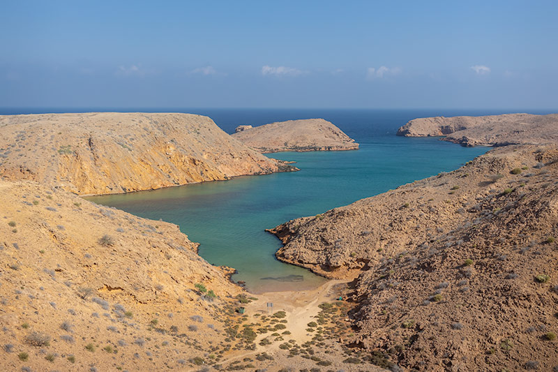 The viewpoint at Bandar Al Khiran in Oman. The sparkling turquoise blue inlet stretches past low sandy mountains out to sea.