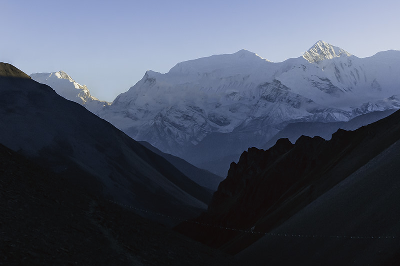 The last bit of sun for the day hits the snowy peak of a mountain in the Annapurnas