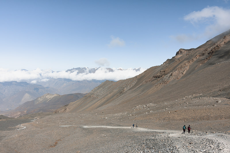 Trekkers descending on a gently sloping trail after Thorong La on the Annapurna Circuit