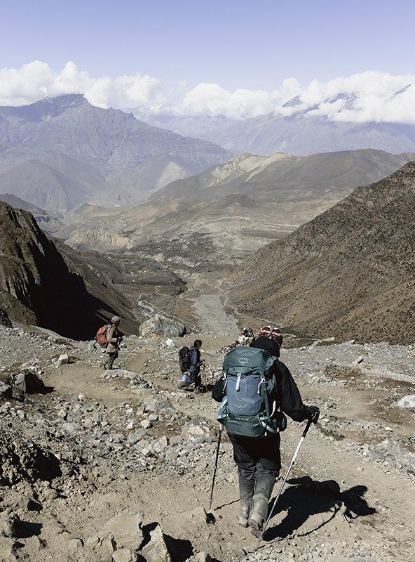 Trekkers descending a steep rocky trail towards Muktinath on the Annapurna Circuit