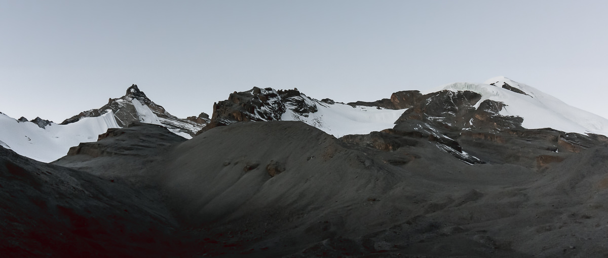 Dry rocky mountains with patches of thick snow at dawn, as seen while ascending to Thorong La