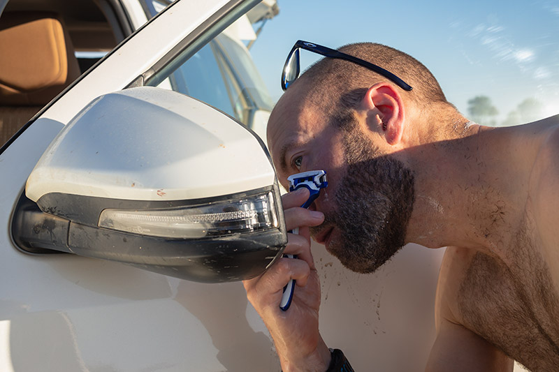 Del tidies up his beard with the aid of the car's wing mirror - needs must on an Oman camping road trip