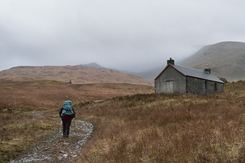 A hiker walks up the stony path on an overcast day towards Tomsleibhe Bothy on the Isle of Mull.