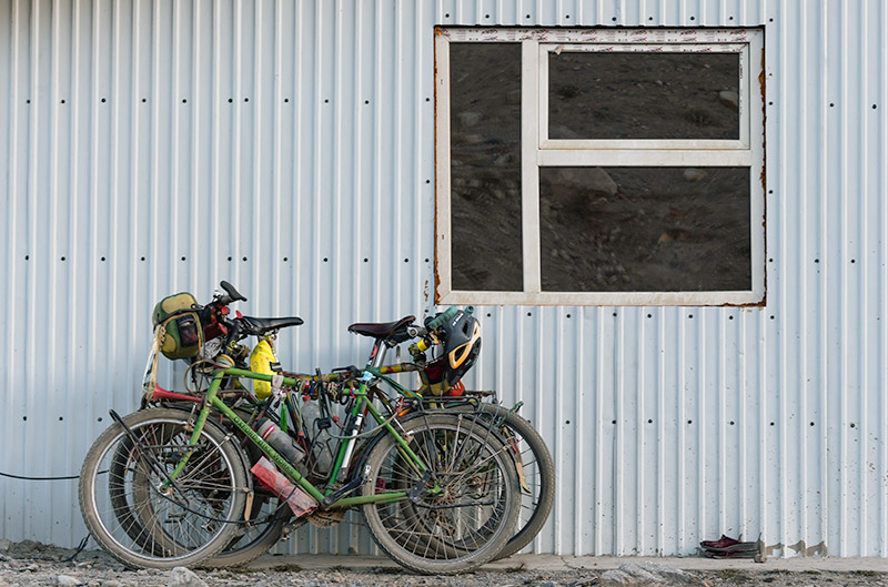 Three Pamir Highway touring bikes resting against the corugated wall of the Jarty Gumbez Guesthouse