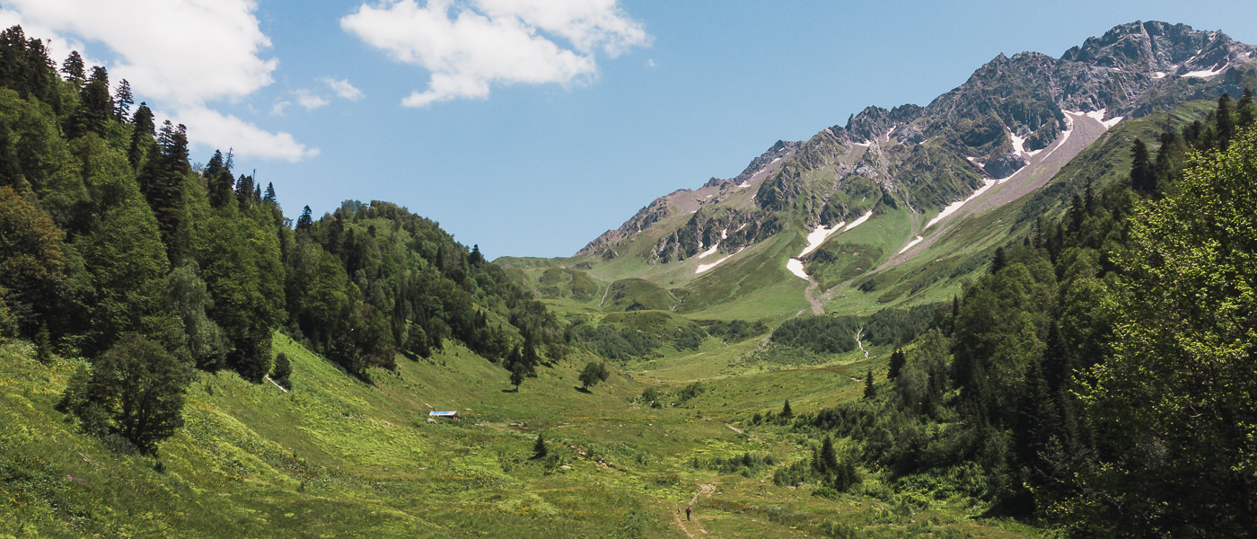 A wide open green valley with mountains behind is the view you are greeted with when you emerge from the forest on Day 1 of the Chuberi to Mestia section of the Transcaucasian Trail in Svaneti, Georgia
