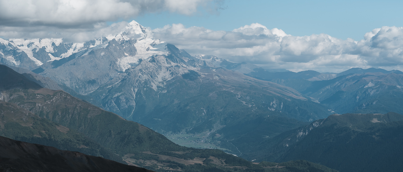 The snowy peak of Tetnuldi showing through the clouds, seen from Gul Pass on the Chuberi to Mestia section of the Transcaucasian Trail in Svaneti
