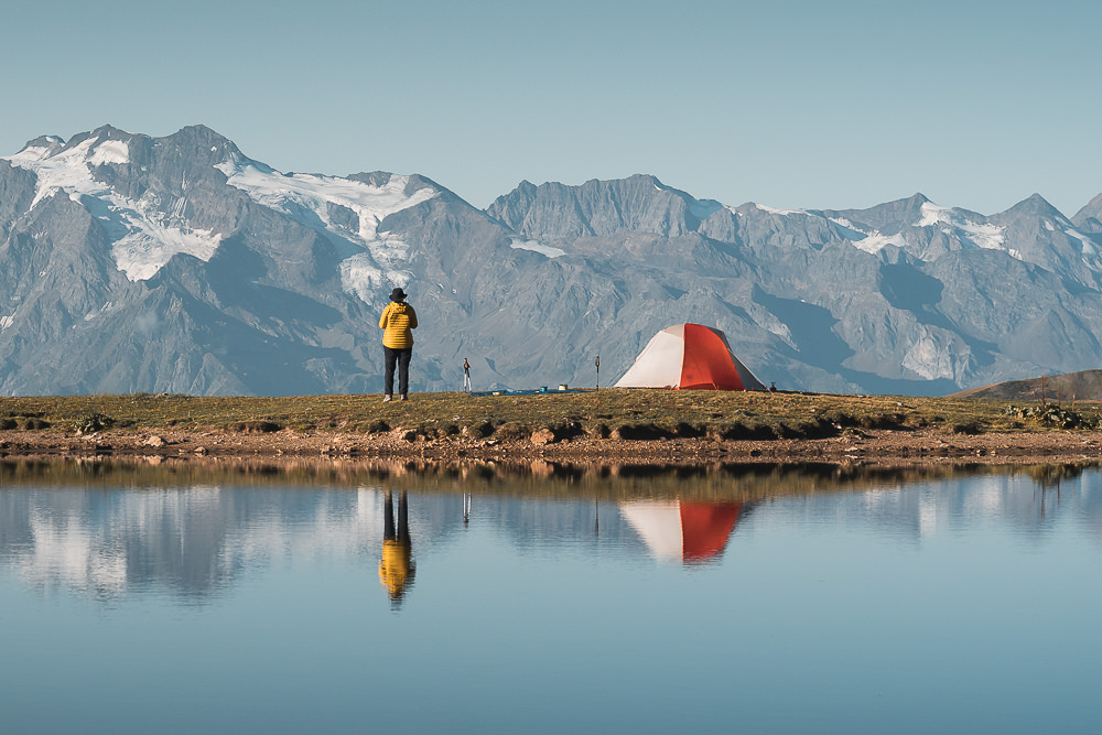 A hiker, tent and mountains reflected in one of the Koruldi Lakes, a worthwhile side trip from the Chuberi to Mestia section of the Transcaucasian Trail in Svaneti