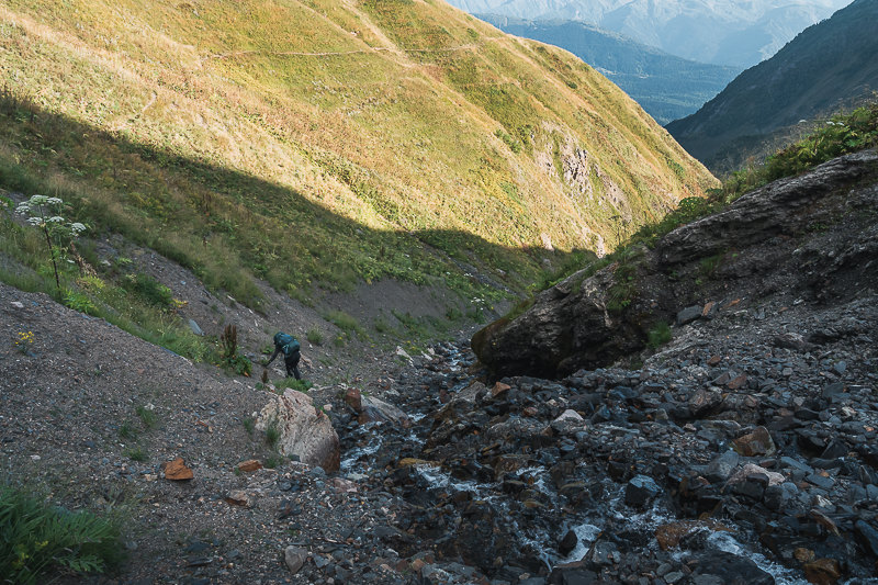 A hiker crossing the Pushkueri gully on the Chuberi to Mestia section of the Transcaucasian Trail in Svaneti