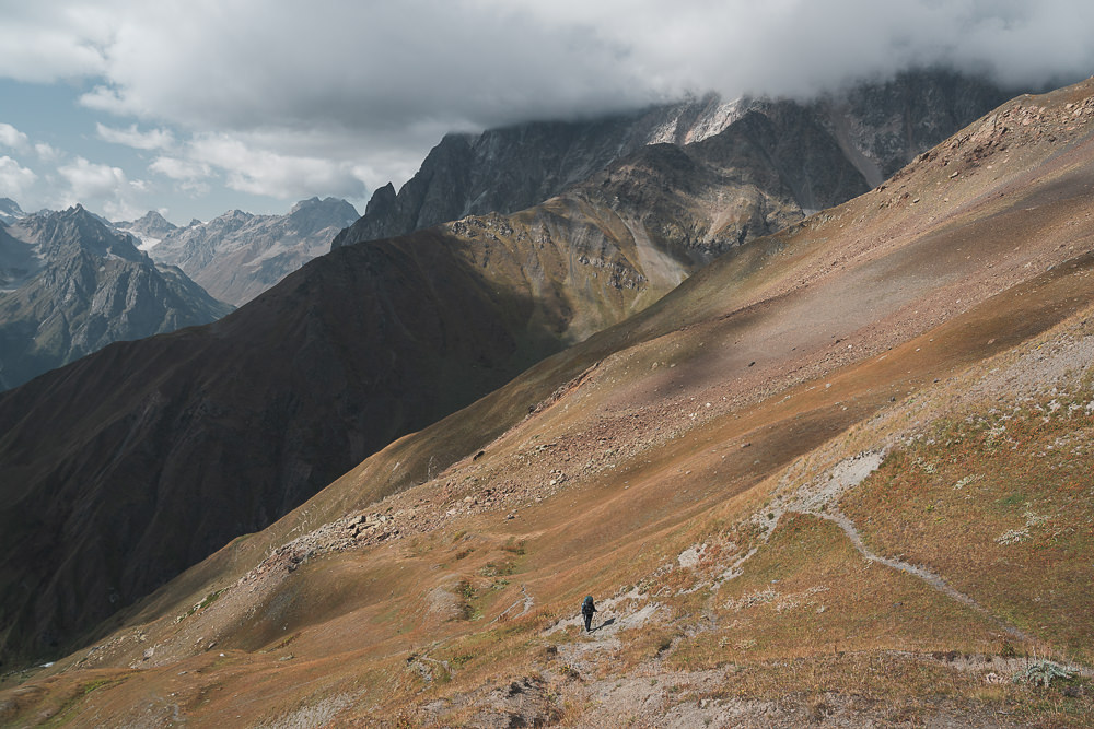 A hiker on the steep final approach to Gul Pass, on the Chuberi to Mestia section of the Transcaucasian Trail in Svaneti