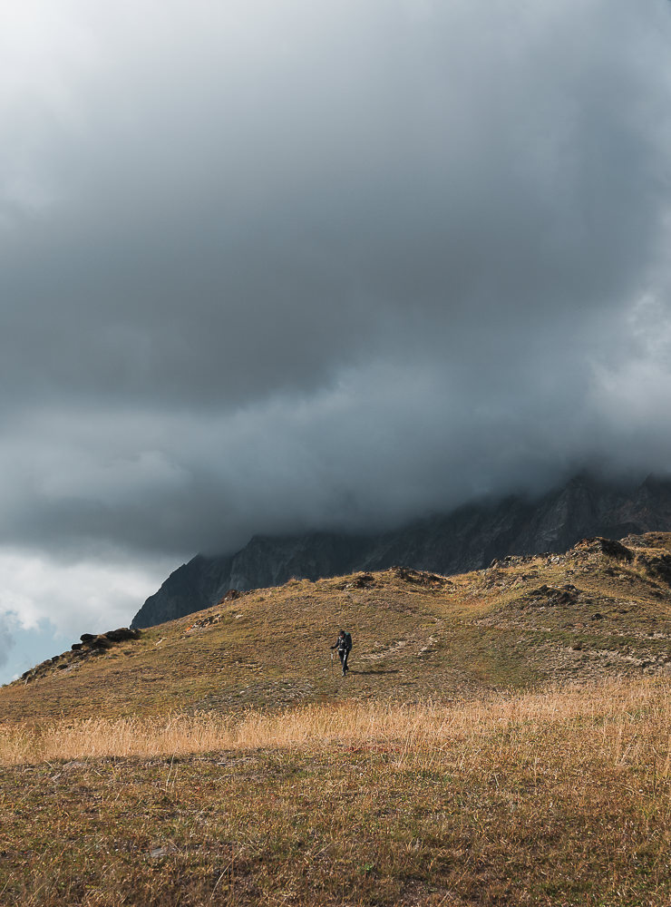 A hiker descending along the ridgeline from Gul Pass, on the Chuberi to Mestia section of the Transcaucasian Trail in Svaneti