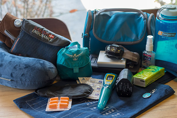 Essential Things to Pack for Travelling: all the essential travel items displayed on the table