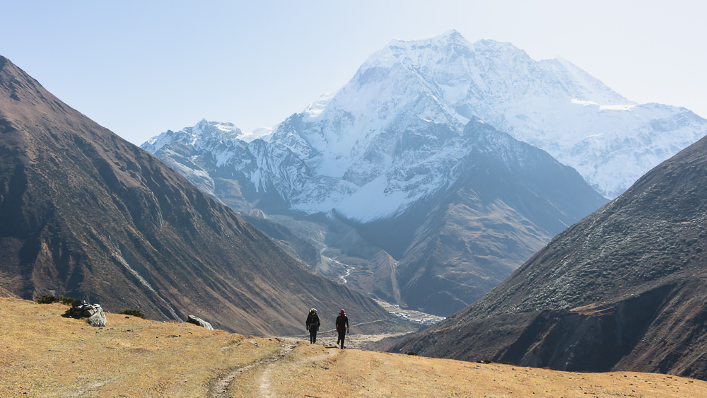A trekker and guide are climbing the trail from Samdo to Dharamsala on the Manaslu Circuit, with snowy peaks behind and Samdo a tiny speck below