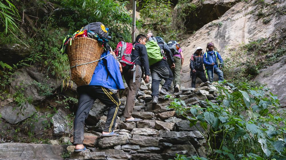 Trekkers, guides and porters climbing stone steps on the Manaslu Circuit Trek