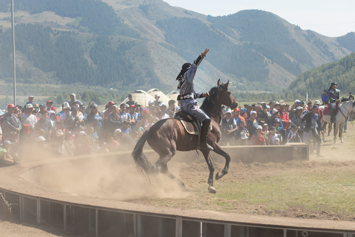 A trick rider at the World Nomad Games in Kyrgyzstan takes the crowd's acclaim after an skillful show of acrobatics. He is raising one hand aloft in acknowledgment as his horse kicks up a huge cloud of dust from the dry ground.