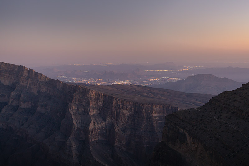 A twilight view of the mountains and twinkling lights of the distant towns. A reason to camp on the rim of Oman's grand canyon at Jebel Shams, one of the best campsites in Oman.