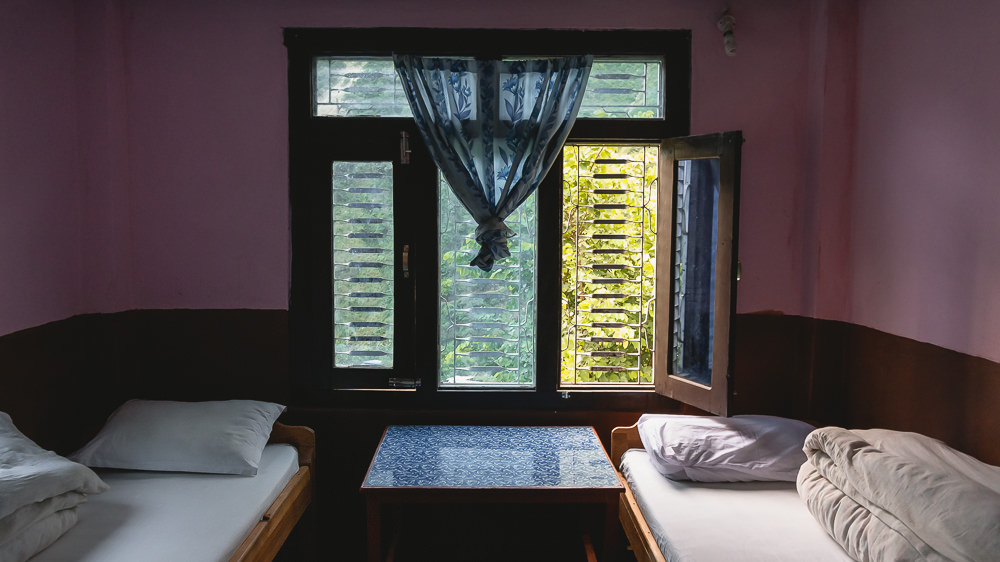 A twin room with two single beds, a small table and a window at the Larke Peak Hotel in Machakhola on the Manaslu Circuit Trek