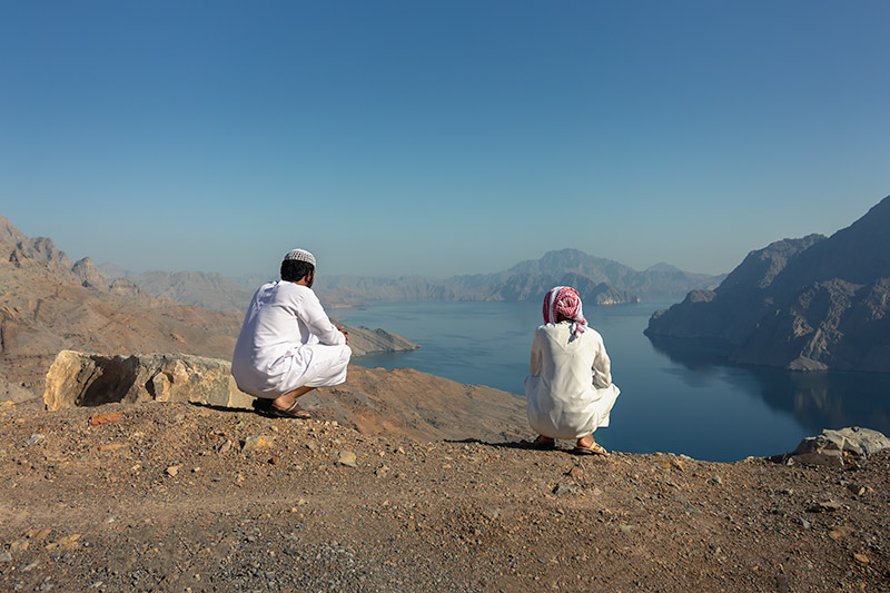 Two young men resplendent in sparkling white dishdashas look out over the famous Khor Najd in Musandam, Oman