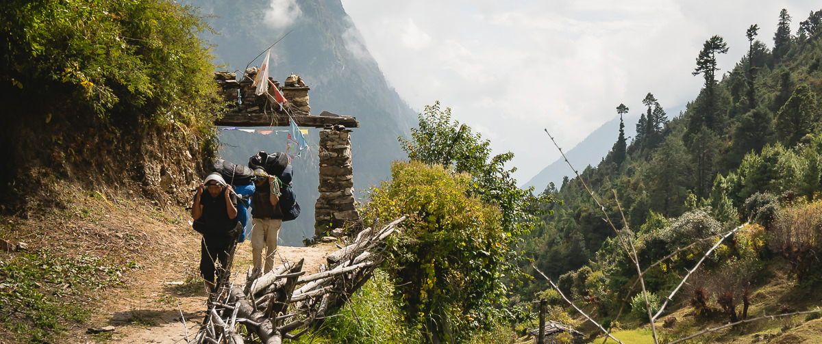 Two porters carrying heavy loads on the Manaslu Circuit