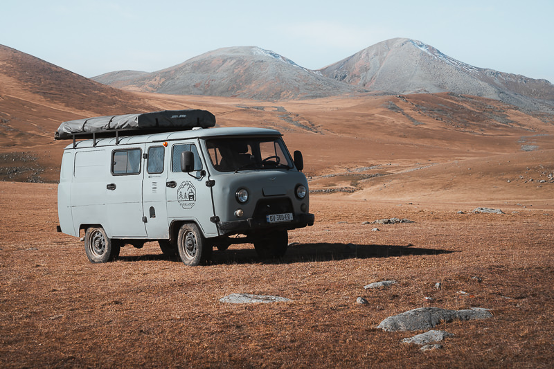 A UAZ Buhanka campervan parked up on the grassy slopes of the Javakheti Plateau in Georgia