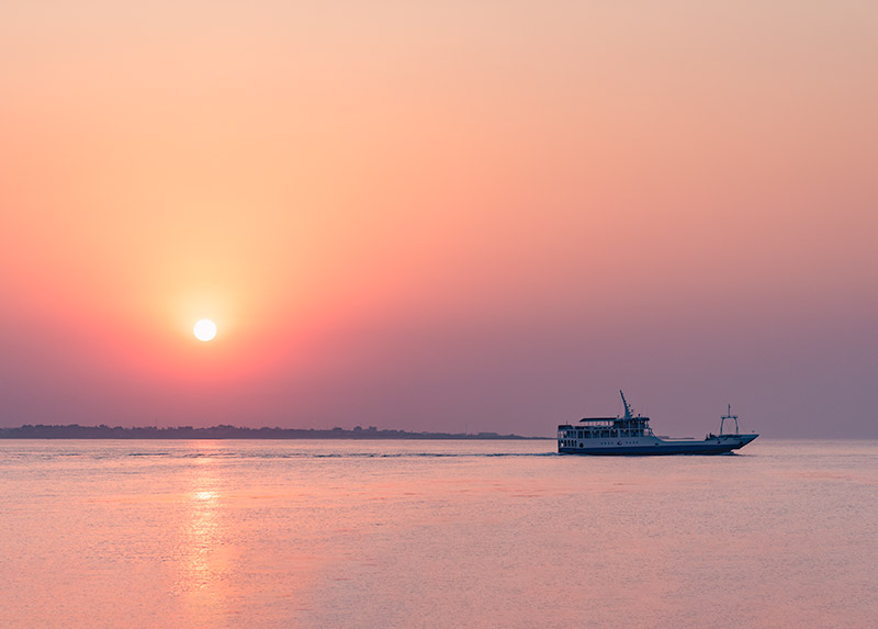 A sunset going down behind a ferry sailing across the sea
