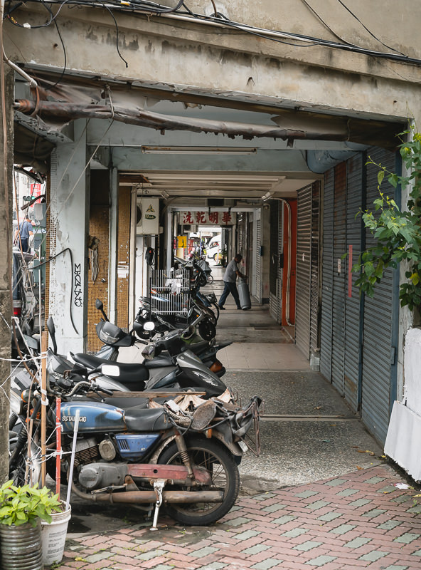 Undercover footpath on a Tainan street with a characteristic row of motorbikes, shuttered shop fronts and a man delivering a gas canister