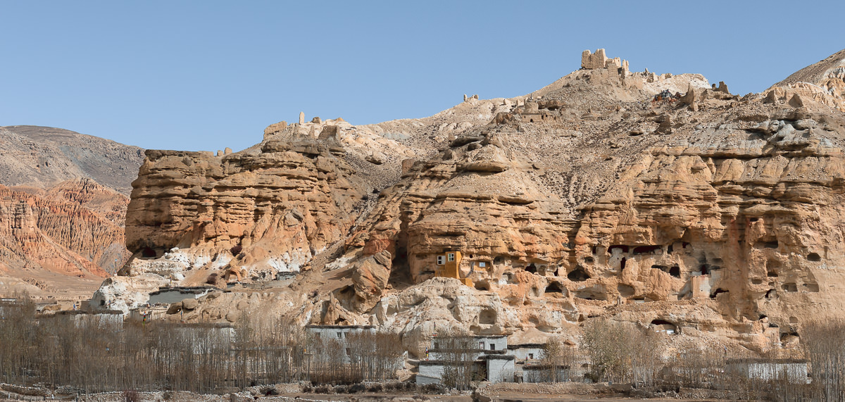 Blocky whitewashed houses, cliffside caves and crumbling ruins at Chhoser in Upper Mustang