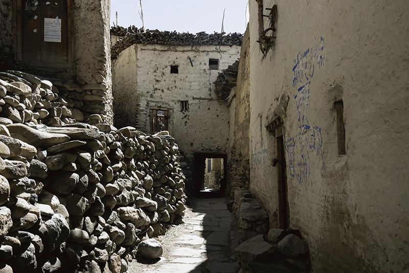 A narrow lane, half in sun half in shadow, leads between whitewashed mudbrick buildings in the Upper Mustang village of Chhusang.