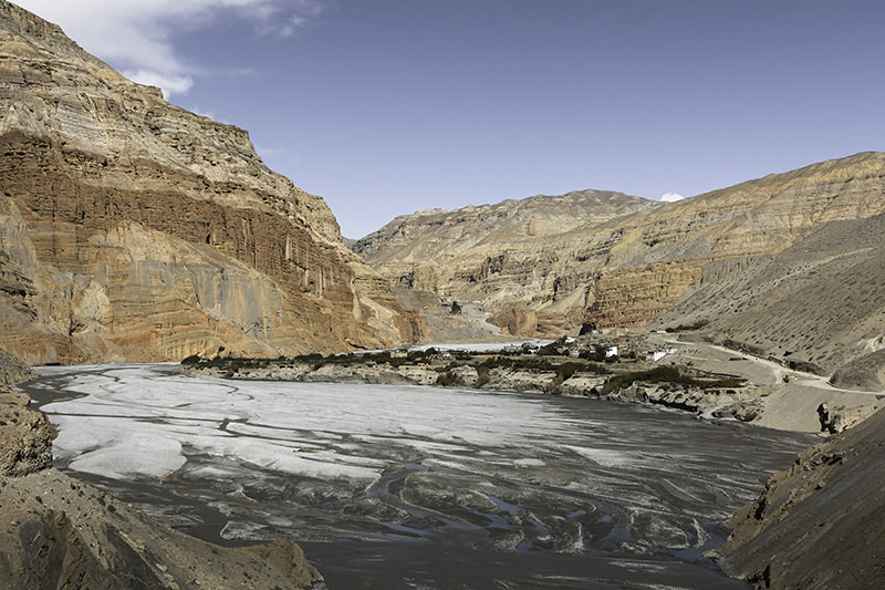 A view down towards the village of Chhusang in the middle of the Kali Gandaki Gorge. The village juts out on a spit of land and red and orange cliffs rise to the side. Seen from the road on the first day of an Upper Mustang trek.