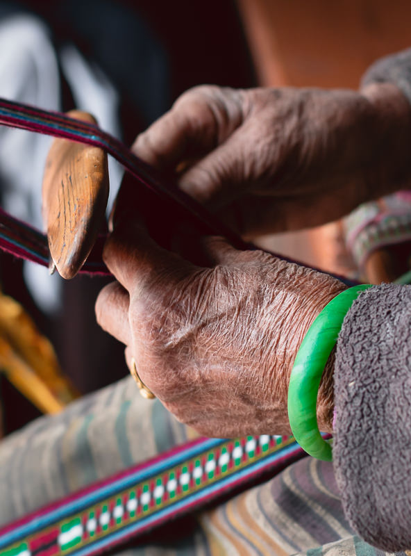 A grandma's aged hands weaving a traditional Upper Mustang belt on a makeshift loom