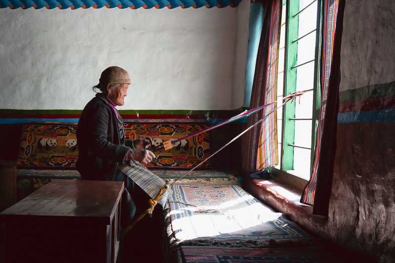 A grandma weaving with a makeshift loom by the window in her home in Dhi, Upper Mustang