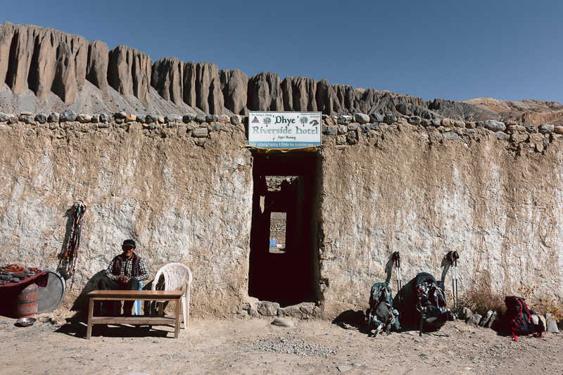 Backpacks propped against the faded whitewashed wall of the Dhye Riverside Teahouse