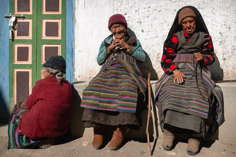 Three elderly women in traditional Tibetan dress sitting in the sun on the streets of Tsarang