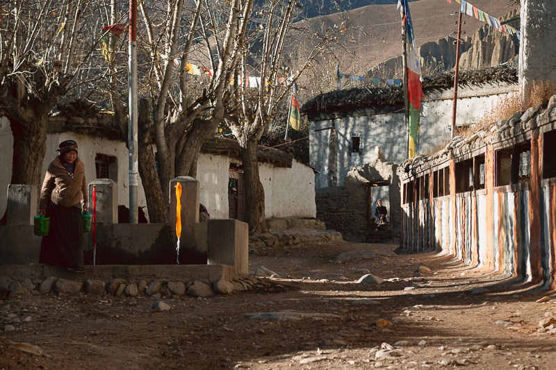 The central square in Ghami with its striped prayer wheel wall and community water taps